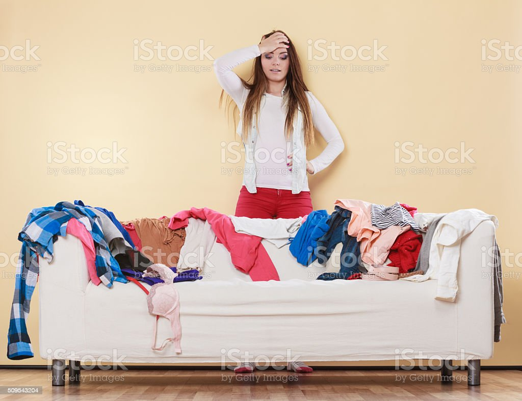 Desperate helpless woman standing behind sofa couch in messy living...