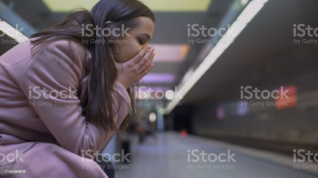 Desperate lady suffering anxiety attack at subway station, feeling...