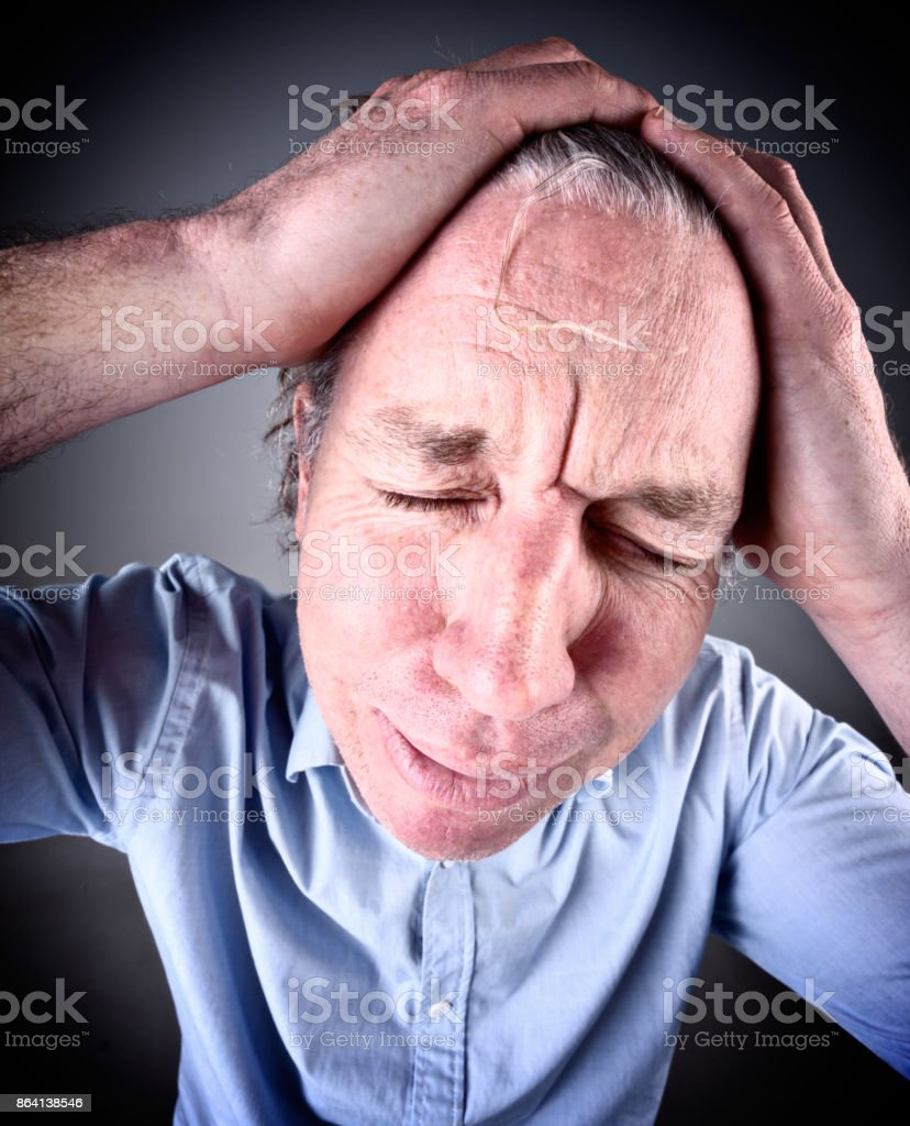 Desperate looking man clutches his head in pain or sorrow royalty-free stock photo