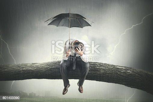 istock desperate man crying under rain 601403390