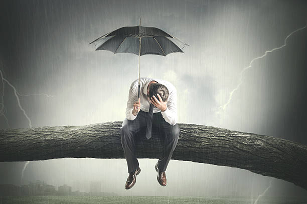 desperate man crying under rain stock photo
