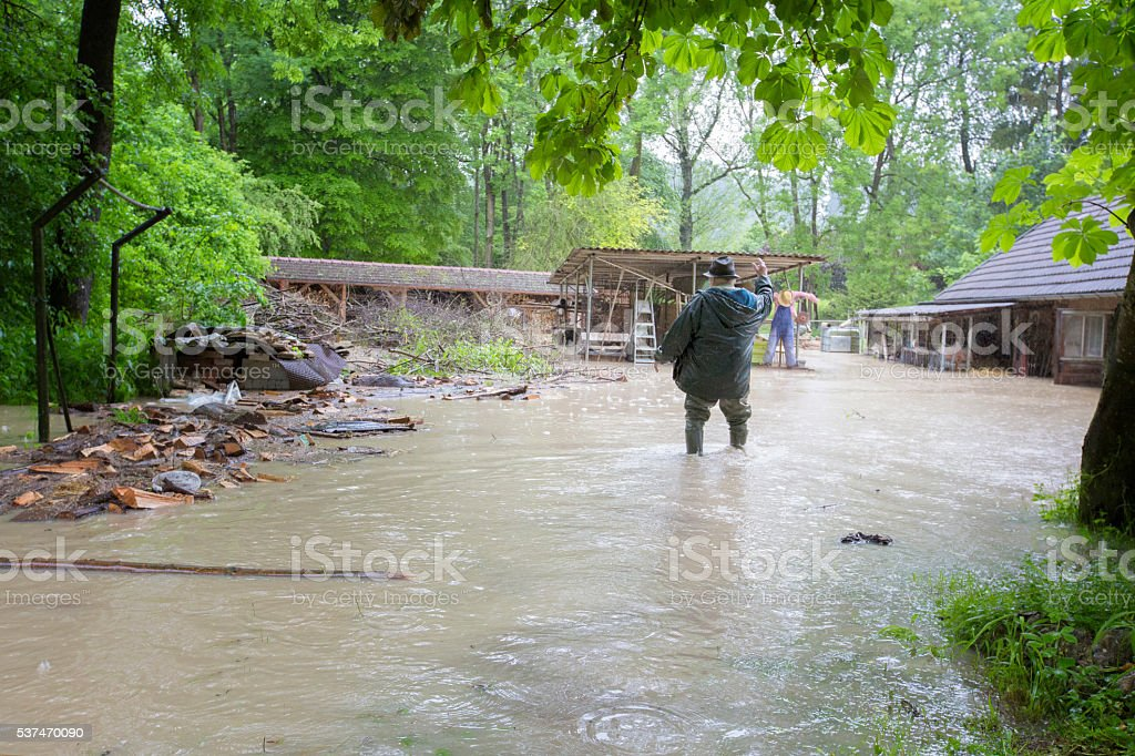 Desperate Man in front of Flooded House stock photo