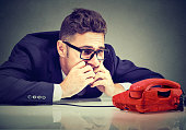 istock Desperate man waiting for someone to call him 1226936529