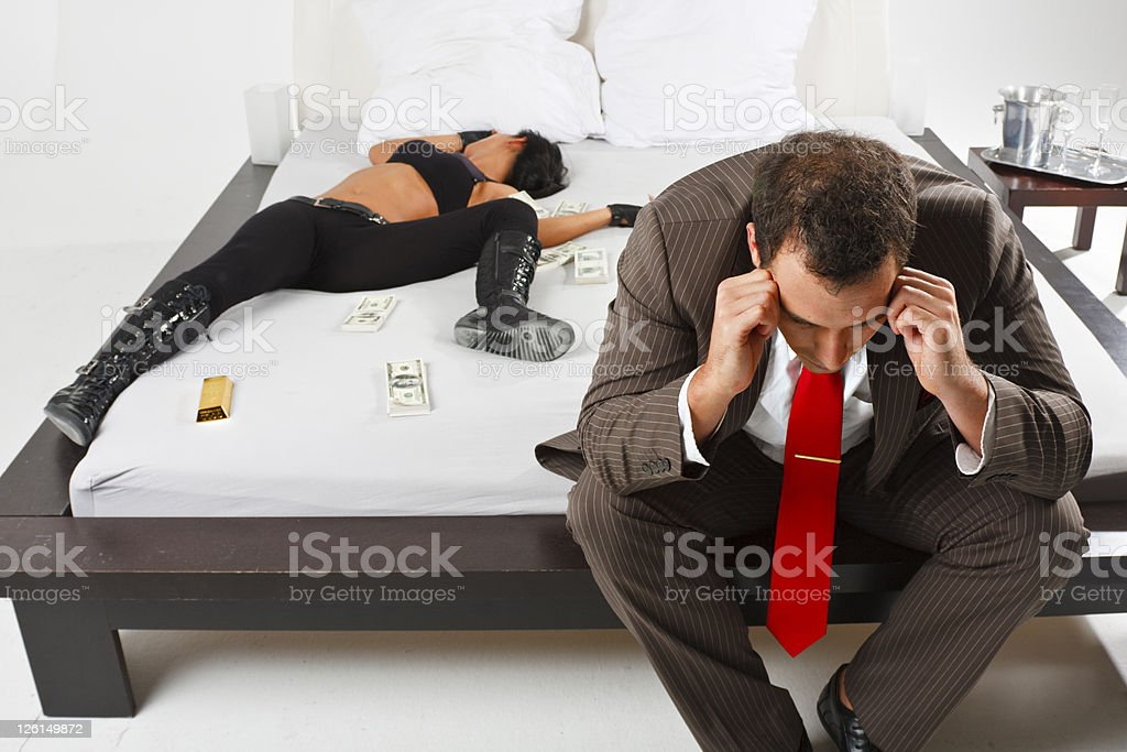 Desperate Man With Money And Beautiful Woman On Bed stock photo