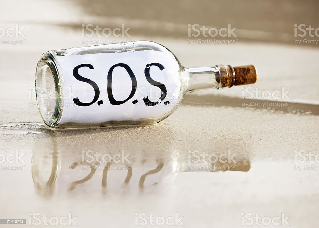 Desperate message in washed-up bottle says SOS royalty-free stock photo