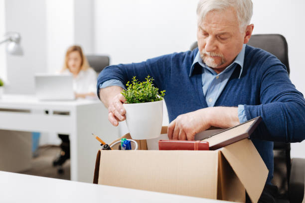 desperate office manager gathering personal stuff into the box - kündigung arbeitsvertrag stock-fotos und bilder