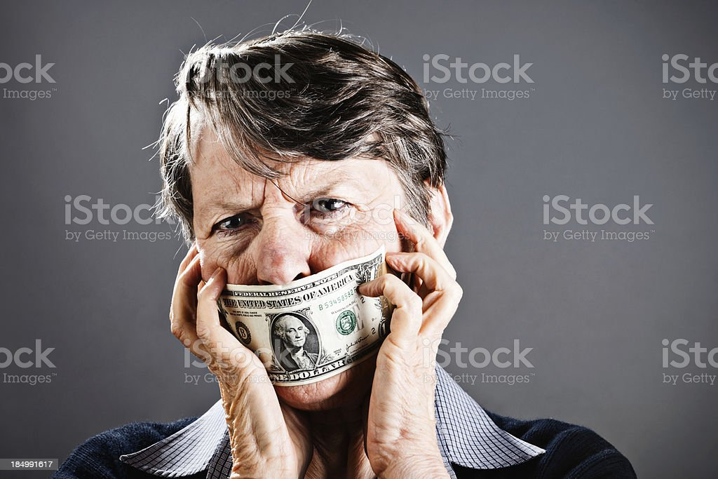 Desperate old woman tries to remove dollar bill gag stock photo