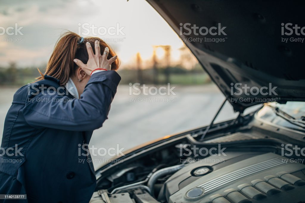Young, stressed woman is looking at her broken car and holding her...
