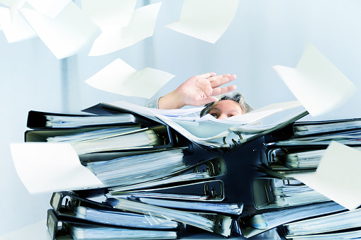 desperate woman behind high stacks of ring binders and lots of papers are flying around in the office, concept of excessive demands and increasing work in business, selected focus, motion blur