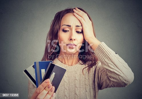 Young woman holding credit cards and looking stressed having financial problems.
