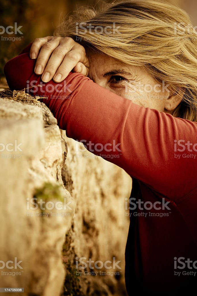 Desperate woman Desperate woman leaning against a rock wall. 50-59 Years Stock Photo