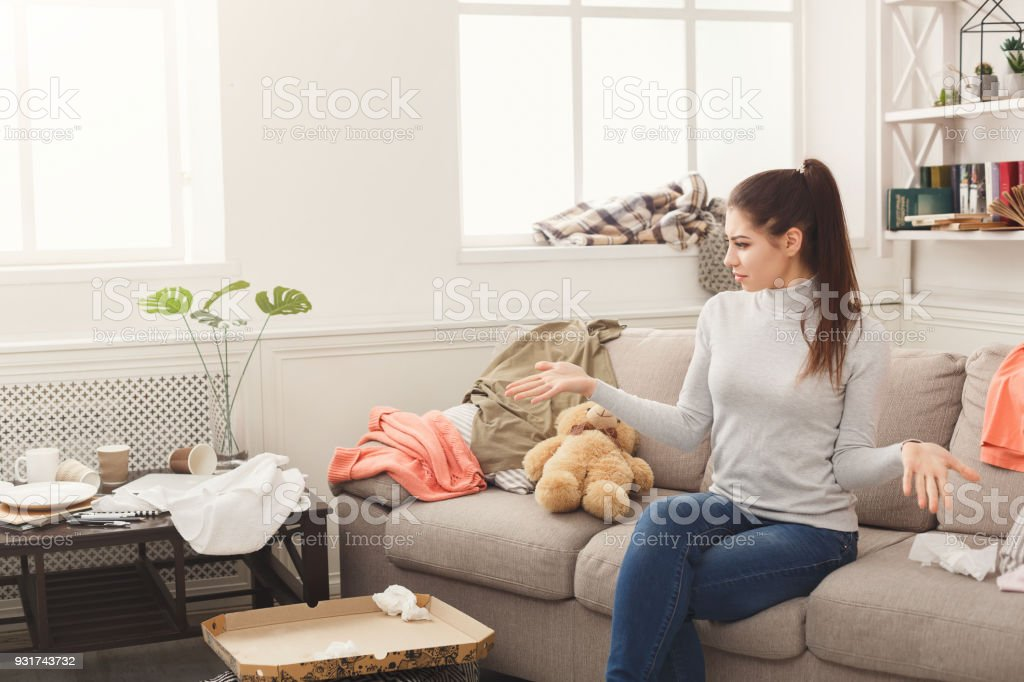 Desperate helpless woman sitting on sofa in messy living room. Young...