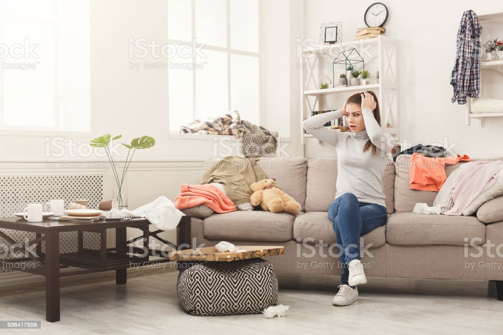 Desperate woman sitting on sofa in messy room stock photo