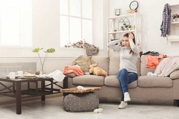 Desperate woman sitting on sofa in messy room Desperate helpless woman sitting on sofa in messy living room. Young girl surrounded by many stack of clothes. Disorder and mess at home, copy space arrangement stock pictures, royalty-free photos & images