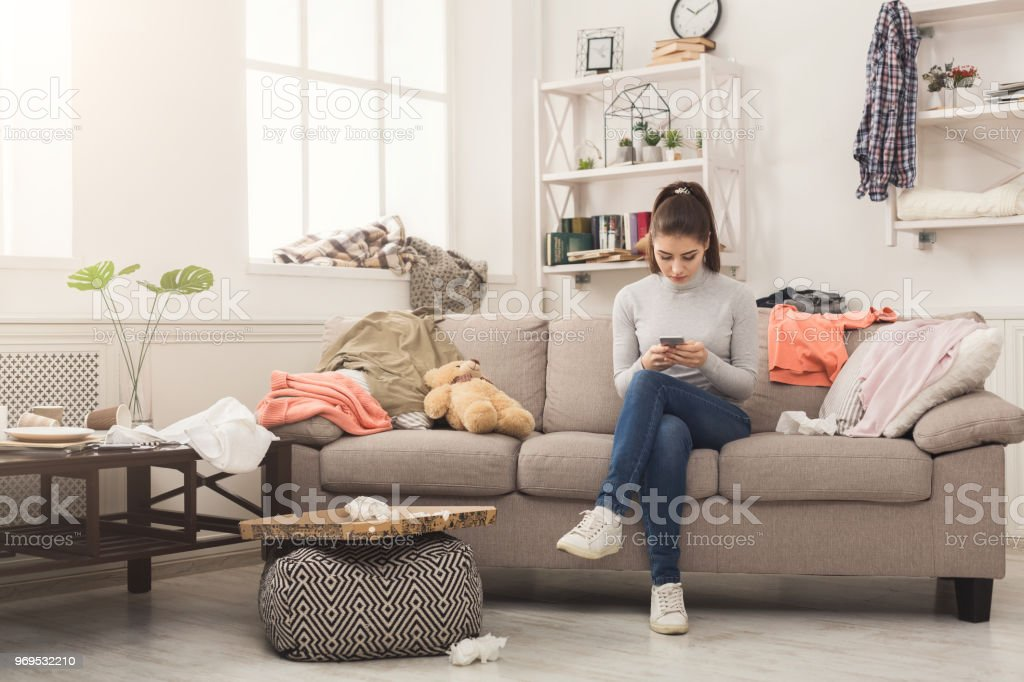 Desperate helpless woman sitting on sofa in messy living room. and...