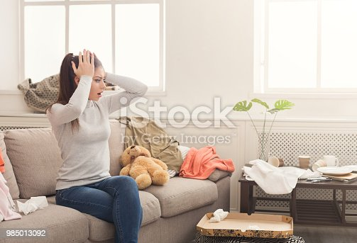 istock Desperate woman sitting on sofa in messy room 985013092