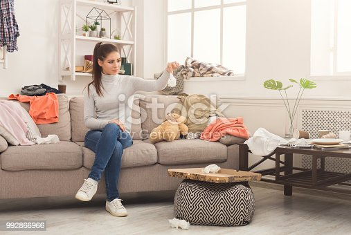 istock Desperate woman sitting on sofa in messy room 992866966