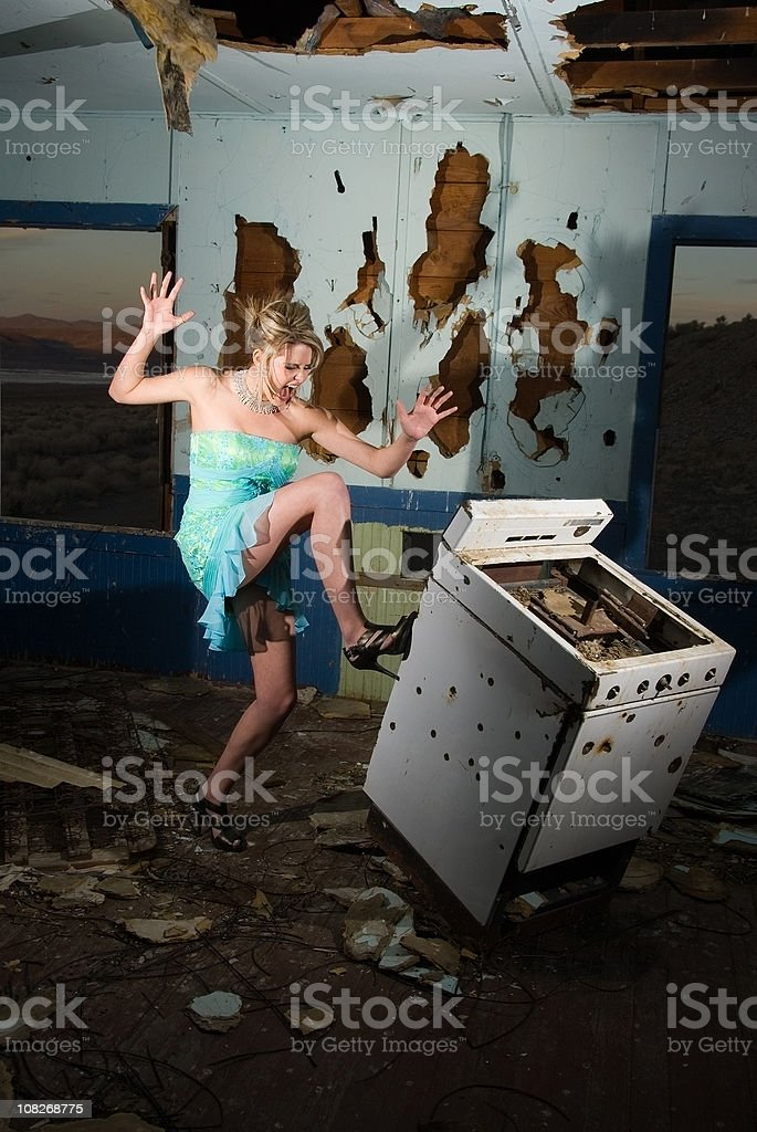 Desperate young blond housewife going berserk inside abandoned house royalty-free stock photo