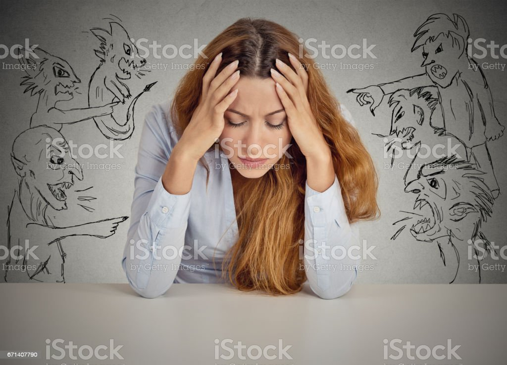 Desperate young businesswoman sitting at desk in her office stock photo