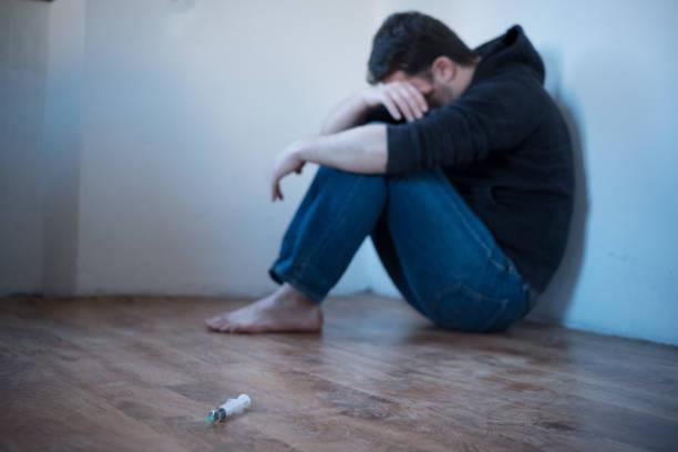 빈 방에 절망적 인 젊은 남자 - 마약 뉴스 사진 이미지