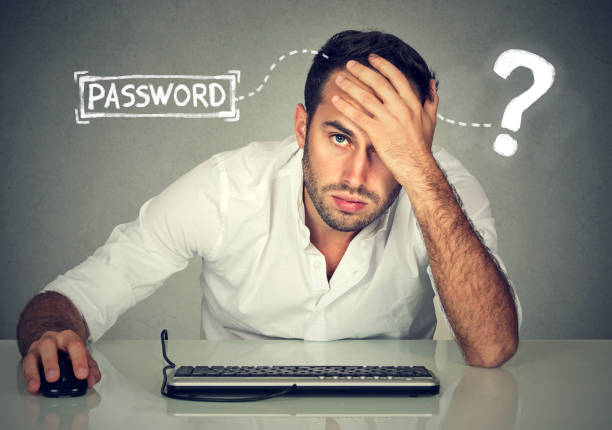 Desperate young man trying to log into his computer forgot password stock photo