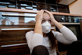 Desperate Young woman portrait wearing a face mask at home during Coronavirus quarantine
