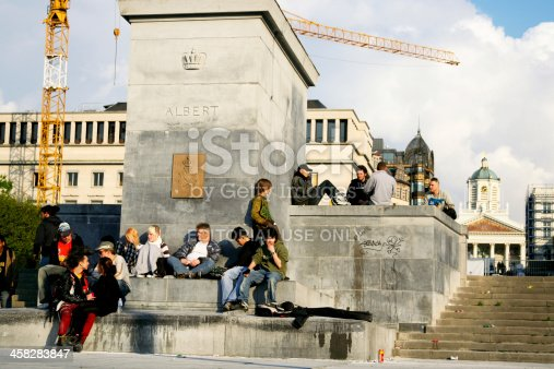 Brussels, Belgium - May, 2nd 2008: Group of young people and some punks are sitting around monument of King Albert at square Place Albertine in center of Brussels. On steps is rubbish. In background are buildimgs of square Kunstberg.