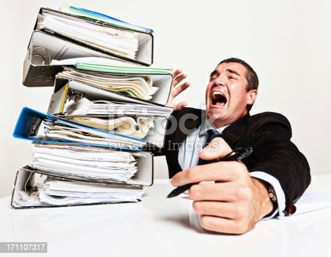 istock Desperately overworked businessman trying to avoid toppling stack of files 171107317