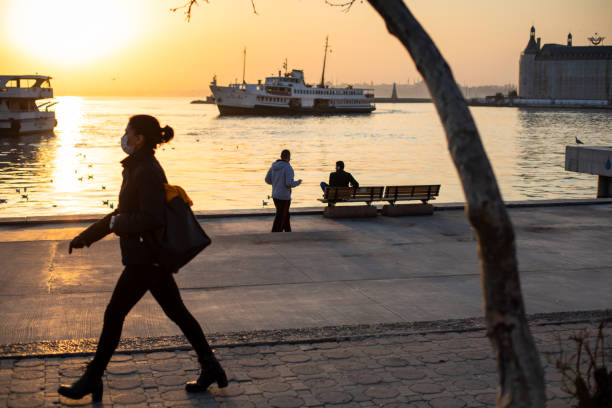 Despite the stay at home warnings due to the coronavirus outbreak, some citizens continued to walk on the Kadikoy coast. stock photo