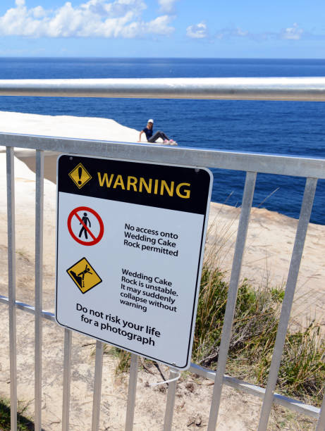 Despite warning signs to stay off the cliff and recent deaths from falls, tourists seeking a selfie climb over the fence at Wedding Cake Rock at Royal National Park Despite warning signs to stay off the cliff and recent deaths from falls, tourists seeking a selfie climb over the fence at Wedding Cake Rock at Royal National Park despite stock pictures, royalty-free photos & images