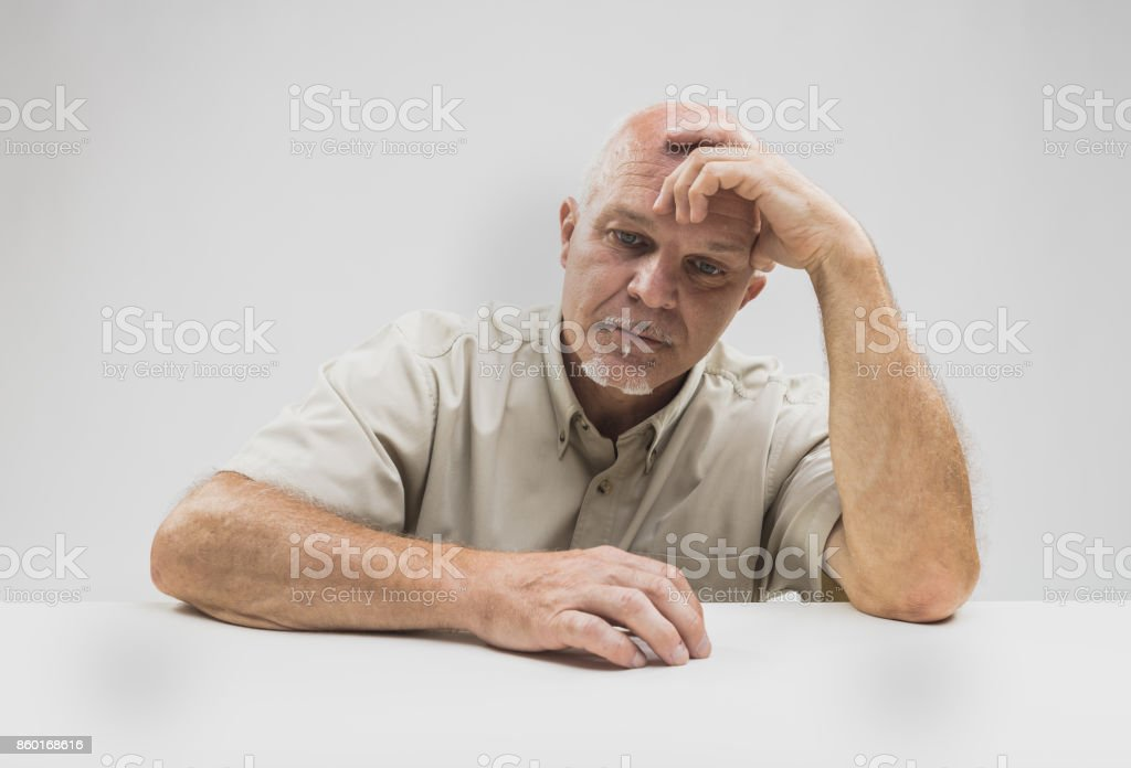 Despondent senior man sitting thinking stock photo