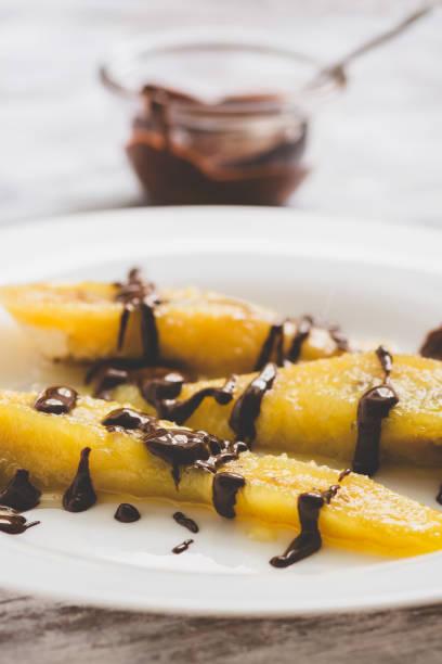 dessert bananen in sirup gegossen mit flüssiger schokolade nahaufnahme. - gebackene banane stock-fotos und bilder
