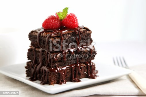SEVERAL MORE IN THIS SERIES. Mini chocolate cake covered with warm chocolate fudge sauce.  Very shallow DOF.