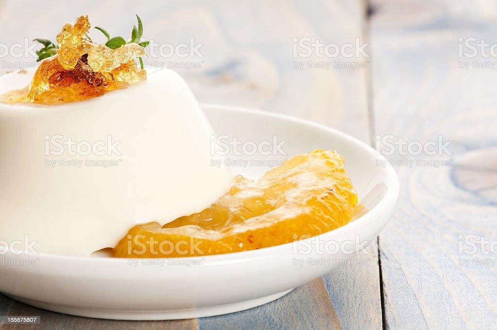 A dessert of vanilla Panna Cotta with lemon and fresh herbs royalty-free stock photo