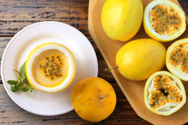 mousse de fruit de passion de dessert dans le dessus de fruit sur l'assiette décorant la table en bois rustique - fruit de la passion photos et images de collection