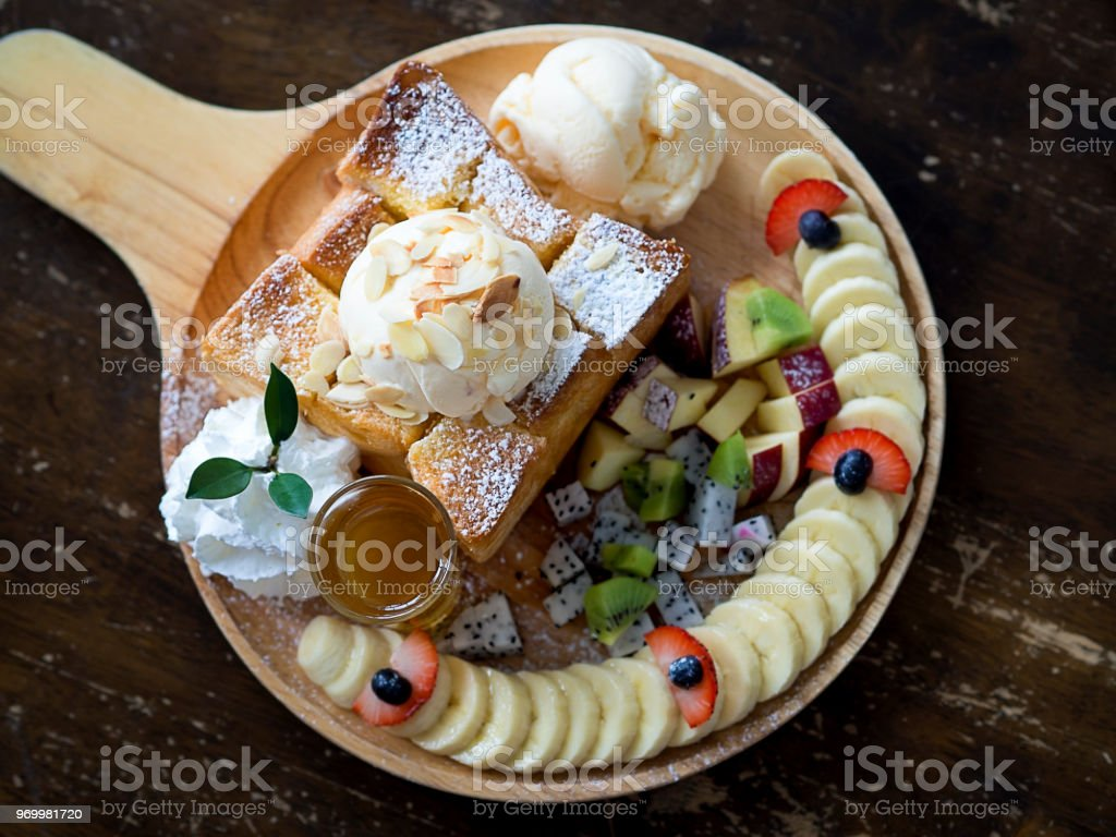 Dessert plate of butter toast with Vanilla ice cream, mix fresh sliced fruits, banana slices and whipped cream on wooden table for dessert, ice cream and sweet menu, top view stock photo