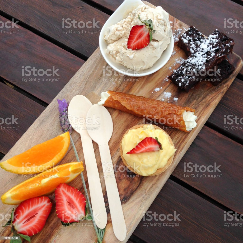 Dessert platter on wooden board with brownies, tart, fruit, brandy snaps and disposable environmentally friendly spoons stock photo