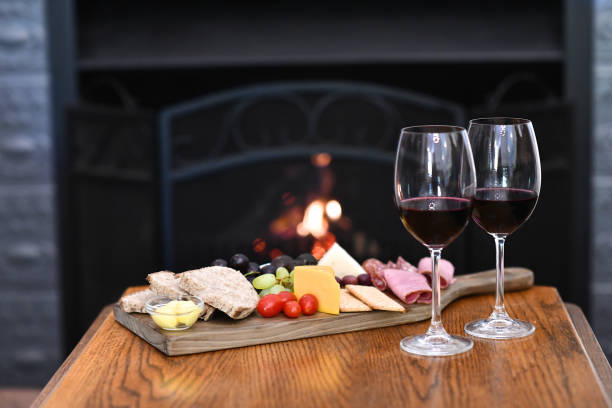 Dessert wine and cheeseboard at fireplace stock photo