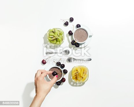 A woman's hand trying to drop fruit into a drink