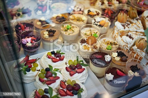 Showcase with many different desserts. Pavlova, tiramisu, cakes and mousses