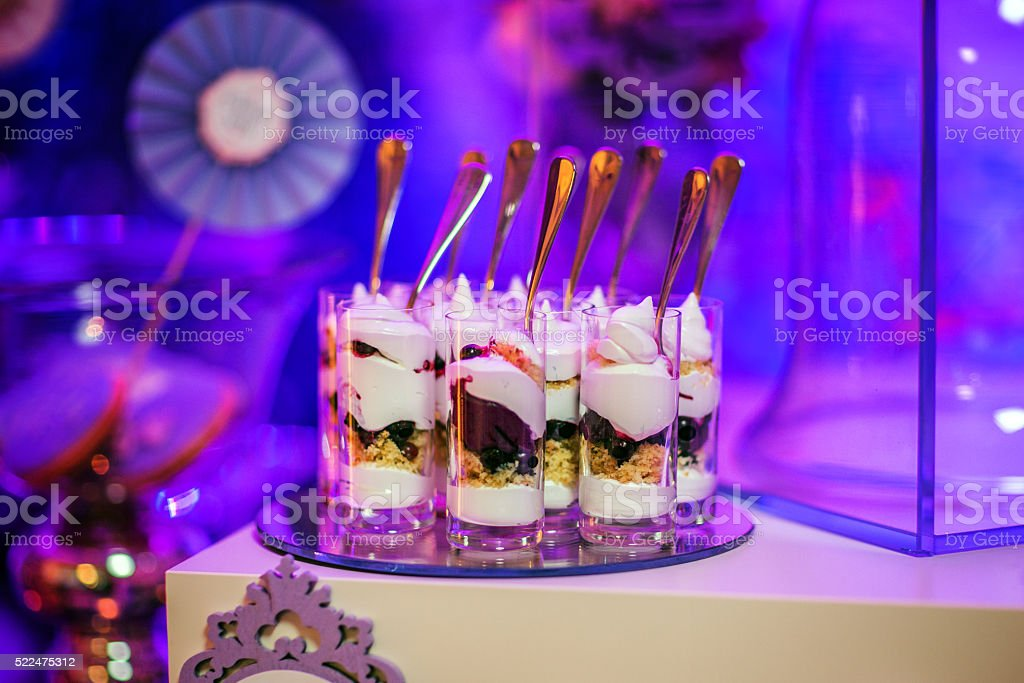 Desserts cream with berry at shot glasses in a row stock photo