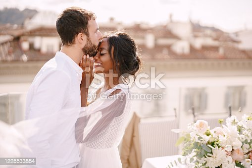 Interracial wedding couple. Destination fine-art wedding in Florence, Italy. Caucasian groom and African-American bride cuddle on the roof, in the sunny sunset light.