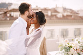 istock Destination fine-art wedding in Florence, Italy. Caucasian groom and African-American bride cuddling on a rooftop in sunset sunlight. Multiracial wedding couple 1225533854