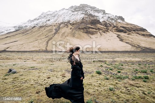The bride in a black dress with a developing train and hair, stands in a field with yellow grass, against the backdrop of a mountain with a snow-capped top.