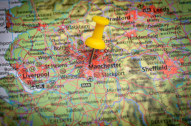Destination Manchester, UK, on geographical map in close up image Detail of the geographic map with yellow pin northwest england stock pictures, royalty-free photos & images