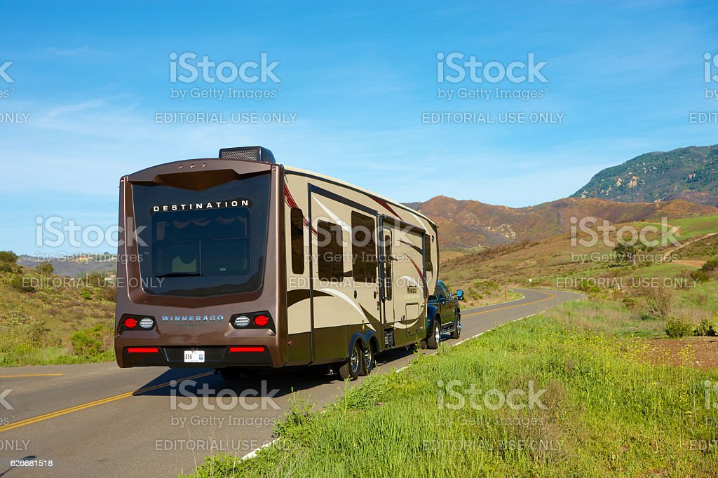 Destinations Winnebago trailer on a mountain road stock photo