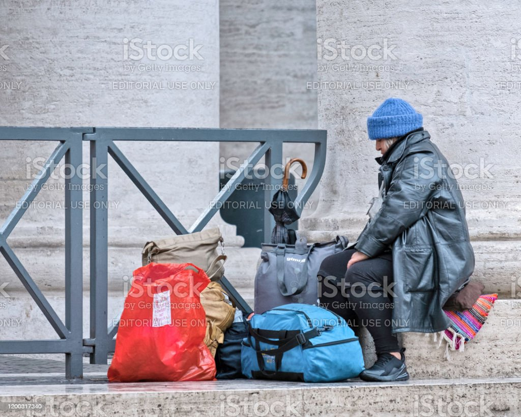 Destitute Rome, Italy - December 19, 2019: A lady sitting on a step in Saint Peter's Square, Rome next to various sorts of baggage. Because of the location it is highly likely these are her entire worldly possessions. Adult Stock Photo