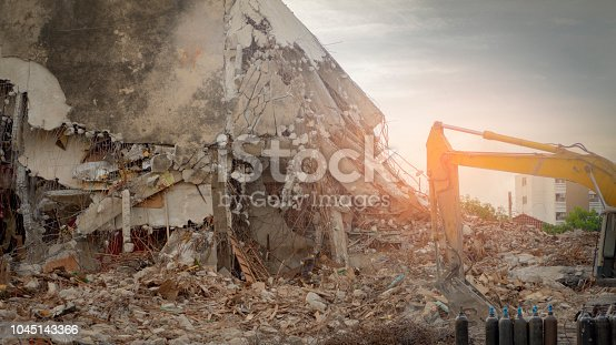 Destroyed building industrial. Building demolition by explosion. Abandoned concrete building with rubble and scrap.   Yellow backhoe working in destruction site.