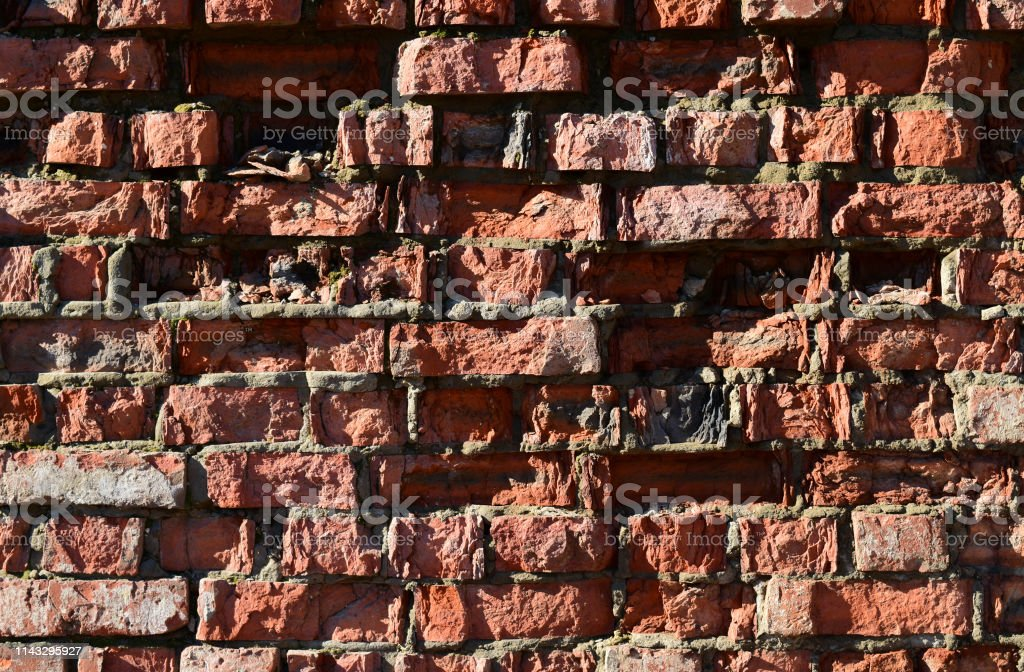 Destroyed by time and precipitation brick wall. The Background of old...