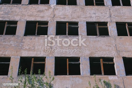 istock Destroyed multi-storey building with many broken windows. 1070593306